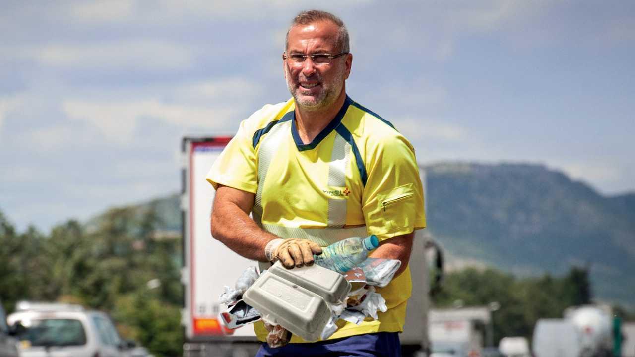 Agent d'autoroute ramassant des déchets sauvages